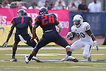 Nevada running back James Butler (20) runs against Arizona's Tellas Jones (1) and Anthony Lopez (28) during the first half of an NCAA college football game in Reno, Nev. on Saturday, Sept. 12, 2015. (AP Photo/Cathleen Allison)