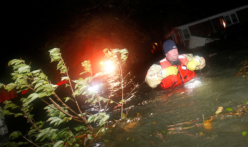 Manasquan firefighter Sean Price wades through chest-high water to rescue trapped residents from homes in an area of the borough which was not under a mandatory evacuation order as Hurricane Sandy hits the Jersey Shore.  (10/29/2012)