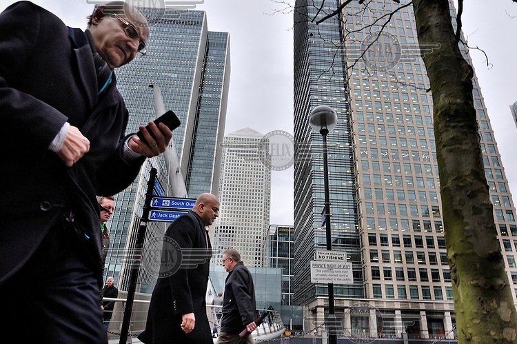 A man, walking beneath the skyscrapers of Canary Wharf, London, uses his mobile phone.