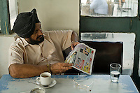 A man reads his newspaper in the Indian Coffee House, Baba Kharak Singh Marg, New Delhi.