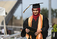 Graduate Haadiya Muhammad walks off of a platform after receiving her diploma, Friday, July 17, 2020 during a graduation ceremony at Bentonville High School in Bentonville. Check out nwaonline.com/200718Daily/ for today's photo gallery. <br /> (NWA Democrat-Gazette/Charlie Kaijo)
