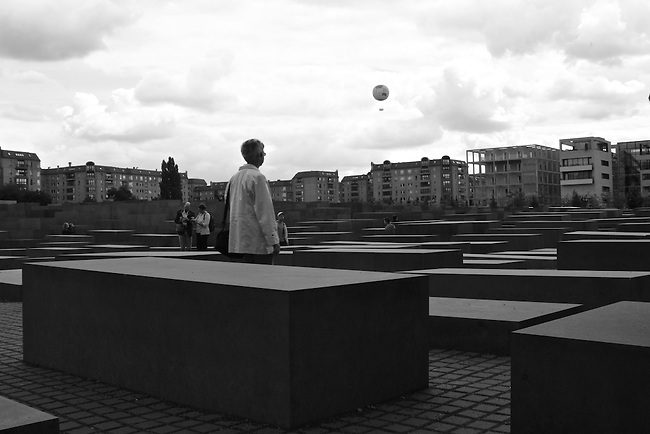 A woman at the Holocaust Memorial in Berlin, Germany watches a hot air balloon float over the city. Aug. 1, 2007.