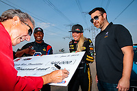 Jun 2, 2018; Joliet, IL, USA; NHRA top fuel driver Leah Pritchett and Antron Brown look on as team owner Don Schumacher signs a check during qualifying for the Route 66 Nationals at Route 66 Raceway. Mandatory Credit: Mark J. Rebilas-USA TODAY Sports