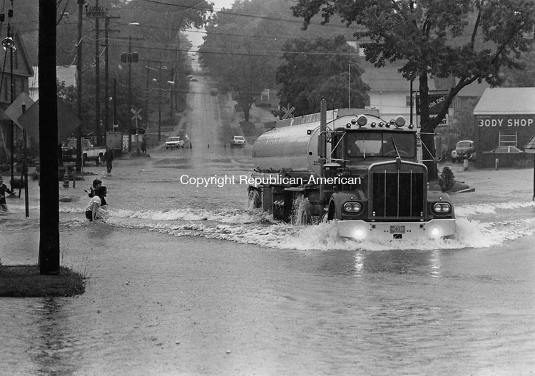 A truck plows through three feet of water on West Main Street in Cheshire during flooding in the spring of 1982.