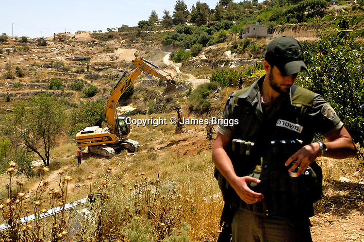 Israeli border police offers stand guard as an Israeli bulldozer uproots Palestinian olive trees during the construction of Israel's controversial West Bank barrier in the village of Al Walaja near Bethlehem on 08-06-2010.