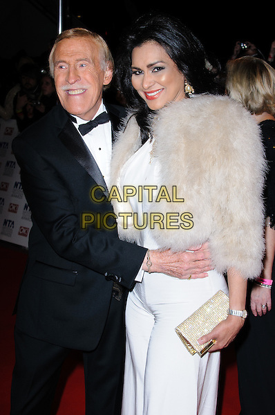 Bruce Forsyth and Wilnelia Merced.arrivals at The National Television Awards, O2 Greenwich, London, England. 25th January 2012.NTA NTAS half 3/4 length dress  suit black white beige fur married husband wife hand arm around waist moustache mustache facia hair clutch bag.CAP/CJ.©Chris Joseph/Capital Pictures.