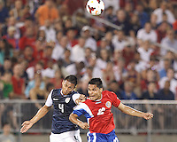 USMNT defender Michael Orozco (4) and Costa Rican forward Jairo Arrieta (22) battle for head ball.  In CONCACAF Gold Cup Group Stage, the U.S. Men's National Team (USMNT) (blue/white) defeated Costa Rica (red/blue), 1-0, at Rentschler Field, East Hartford, CT on July 16, 2013.