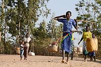 ETHIOPIA Province Benishangul-Gumuz, town Debate, Gumuz women carrying goods with yoke from the market to their village / AETHIOPIEN, Provinz Benishangul-Gumuz, Stadt Debate, Gumuz Frauen mit Tragjoch gehen zum Markt