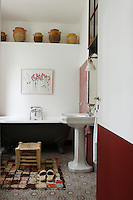 A collection of antique ceramic jars is displayed in an alcove above the old-fashioned roll-top bath in the bathroom