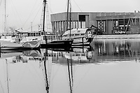 black and white photography of wooden sailboats anchored up for the winter in the part of Aarhus harbor that is only for wooden sailboats. In the background a new building construction to be used in the sailing tournament in the summer