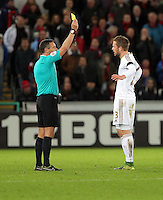 (L-R) Referee Andrew Marriner shown Gylfi Sigurdsson of Swansea a yellow card during the Barclays Premier League match between Swansea City and Bournemouth at the Liberty Stadium, Swansea on November 21 2015