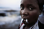 WAGENIA, DEMOCRATIC REPUBLIC OF CONGO MARCH 5: An unidentified young girl keeps her fish in her mouth on March 5, 2006 in Wagenia, a fishing village outside Kisangani, in Congo, DRC. Sh e is fishing in a stream and will later put them in a basket. The village was founded in 1870 and they have been fishing for generations fighting colonialists and nearby tribes. The river is filled with carp, sardines, tilapia, tiger fish and many others. Still young children learn how fish at an early age, and many don&rsquo;t go to school.  Congo is planning to hold general elections by July 2006, the first democratic elections in forty years.<br /> (Photo by Per-Anders Pettersson)