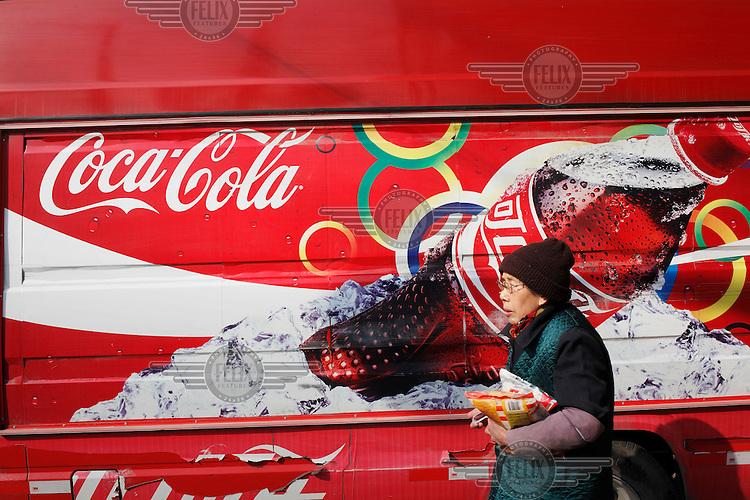 An elderly woman walks past a Coca Cola truck.
