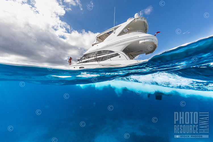 A woman enjoys a gorgeous day in a white power cruiser in the waters of Waikiki, O'ahu.
