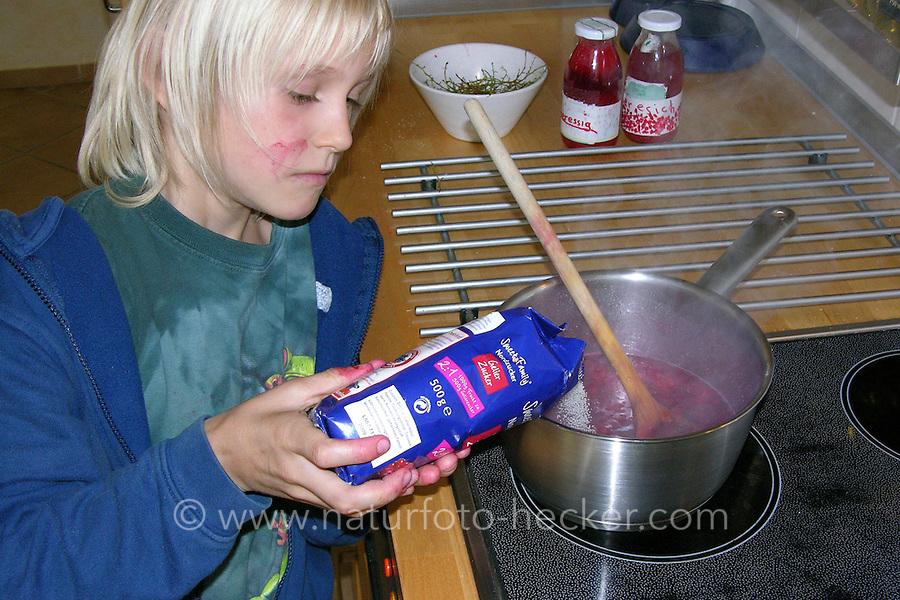 Kind kocht Marmelade, Konfitüre aus Johannisbeeren, Johannisbeere, füllt Gelierzucker zu den Früchten in den Topf, jam