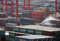 A worker hoses stacks of containers with a liquid while standing on a disinfectant truck at the Yangshan Deep Water Port near Shanghai, China..