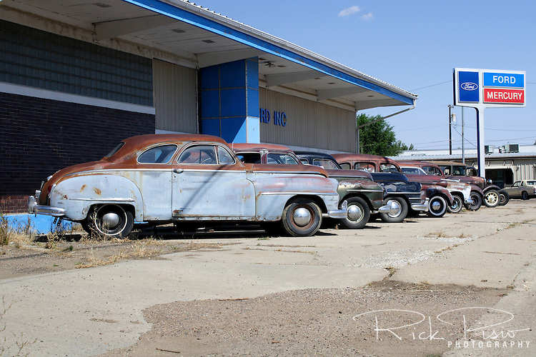 Vintage autos lined up outside a closed Ford dealership in Malta, Montana.
