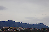From the coastal plane where is the Appia road, under a cloudy sky, a view of the old part of the town of Minturno, that is located on a hill, with the mountains on the background. Digitally Improved Photo.