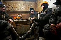Workers from the oil and gas company Bashneft take a break in the 'smoking room' while working on a site in Russia's far north. /Felix Features