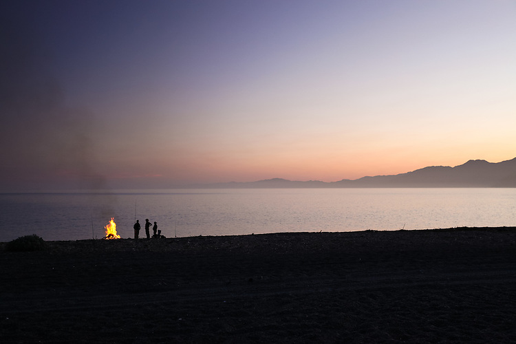 Dusk silhouette of fishermen on South Kaikoura beach with camp fire. New Zealand - stock photo, canvas, fine art print