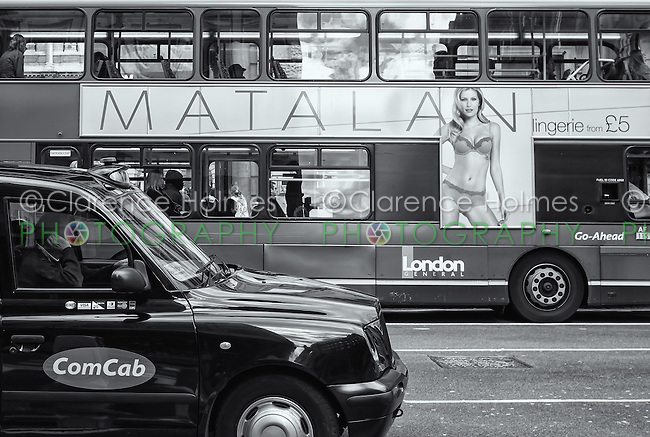 Taxi and double-decker bus in traffic, London, England