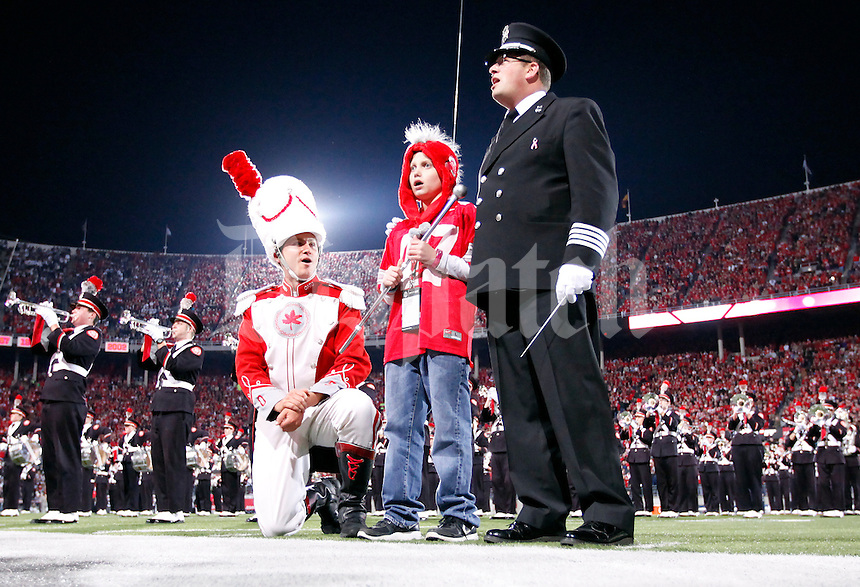 "With drum major Kyle West and director Jon Waters at his side, cancer survivor Grant Reed sings Carmen Ohio with the Ohio State Marching Band prior to the NCAA football game against Penn State at Ohio Stadium in Columbus on Oct. 26, 2013. Reed named his cancer ""Michigan"" and vowed to beat it while in the hospital this past year. His parents were members of the band when they were in college. (Adam Cairns / The Columbus Dispatch)"