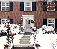 Brick house with garlands and wreath decorated for Christmas in snow, Midwest USA