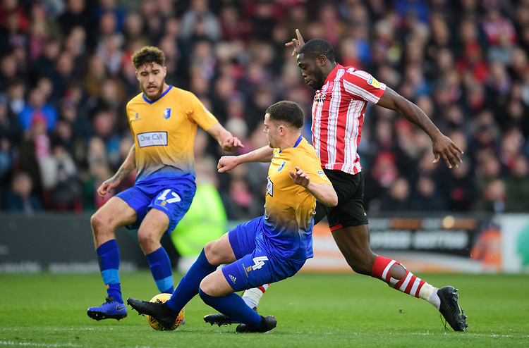 Lincoln City's John Akinde is tackled by Mansfield Town's Matt Preston<br /> <br /> Photographer Chris Vaughan/CameraSport<br /> <br /> The EFL Sky Bet League Two - Lincoln City v Mansfield Town - Saturday 24th November 2018 - Sincil Bank - Lincoln<br /> <br /> World Copyright © 2018 CameraSport. All rights reserved. 43 Linden Ave. Countesthorpe. Leicester. England. LE8 5PG - Tel: +44 (0) 116 277 4147 - admin@camerasport.com - www.camerasport.com