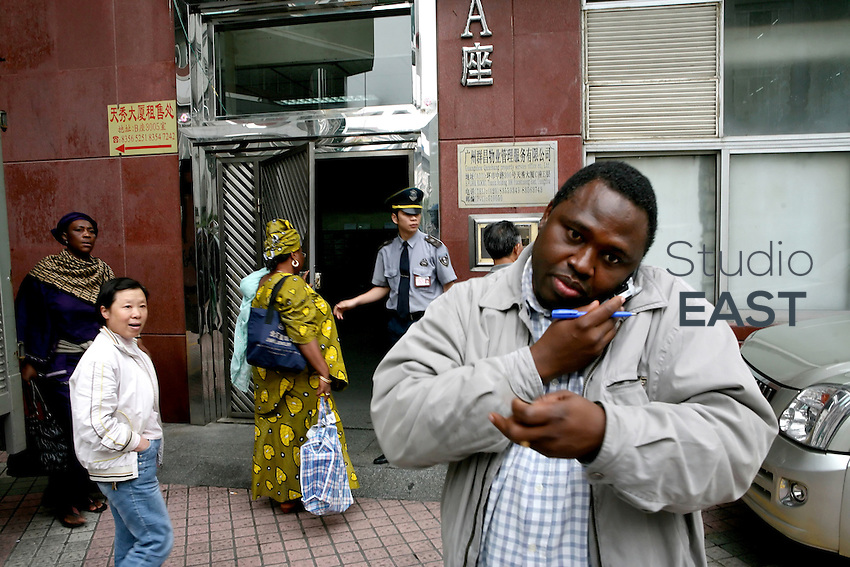"Africans and Chinese pass each other in the courtyard of Tianxiu building, housing African businesses, in Xiaobei Street, the ""African street"" of Guangzhou, China, on March 15, 2007. Chinese goods flow to Africa, but men flow the other way: thousands of Africans are now settling in China. China's Southern metropolis Guangzhou has the country's largest African population, now exceeding 7,000. Photo by Patrick Wack/Pictobank"