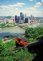 Pittsburgh cityscape with bright red trolley of Desquene Incline on hill in foreground. Pittsburgh Pennsylvania USA.