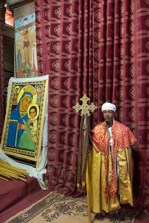 A priest hold a crucifix provides oversight for the colorful murals displayed in one of Lalibela's rock-hewn churches.