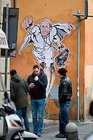 Alcune persone passano davanti l'opera dell'artista di strada Mauro Pallotta che ritrae Papa Francesco nelle vesti di un supereroe. People walk past a graffiti featuring a 'superhero' version of Pope Francis appears in Borgo Pio, next to St. Peter's Square  in Rome. The image started circulating from the twitter account of the Vatican and has rapidly spread around the world.