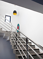 The grey tadelakt staircase has a stainless steel banister and railings.