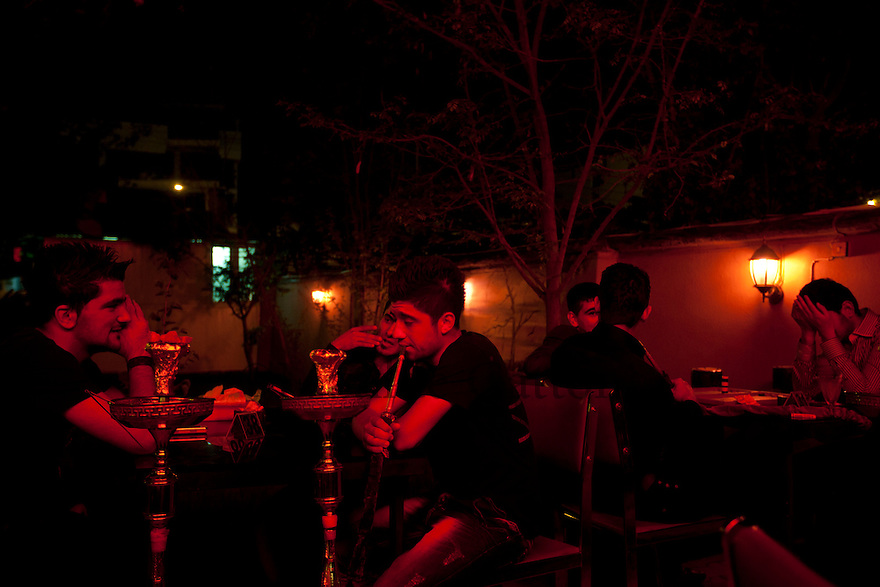 Iraq - Kurdistan - Sulaymaniyah -   Youg men smoking shisha and chatting at night in a cafe'