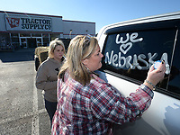 NWA Democrat-Gazette/ANDY SHUPE<br /> Tonya Bryant (right) of Prairie Grove and her daughter, Shai Bryant, write messages about Nebraska Thursday, March 21, 2019, on their pickup with shoe polish while seeking donations of livestock supplies and feed at Tractor Supply in Farmington before heading out to Elkhorn, Neb., to assist in flooding recovery. Bryant plans to return to collect more feed and veterinarian supplies from 8 to 10 a.m. Saturday at Tractor Supply in Farmington before driving back to Nebraska. Bryant is working with No Town Left Behind and Guiding Spirit Animal Rescue Organization in her efforts and plans to make as many trips as necessary until people stop making donations.