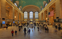Main concourse of Grand Central Station in Manhattan, New York, New York, USA. Originally opened in 1871, the station was completely rebuilt in 1913 and has 44 platforms and 56 tracks. The main concourse is 84x37m and 38m high, and its ceiling is painted with an astrological design by Paul Cesar Helleu, painted by James Monroe Hewlett and Charles Basing. The large American flag was hung in response to the terrorist attacks on the World Trade Center on September 11th 2001. Picture by Manuel Cohen