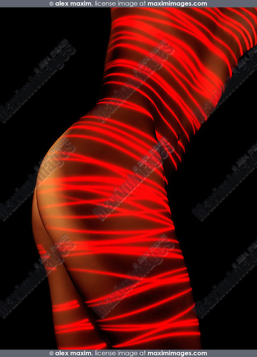 Naked woman body painted with red laser stripes. Isolated on black background. Artistic nude photo.