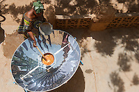 MALI Bandiagara, woman with solar cooker preparing food in village / MALI Bandiagara , Frau bereitet mit Solarkocher das Essen zu