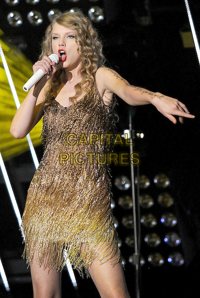 Taylor Swift.2011 CMA Music Festival Nightly Concert held at LP Field, Nashville, Tennessee, USA..June 12th, 2011.stage concert live gig performance music half length gold dress tassels fringed dress singing hand arm pointing .CAP/ADM/LF.©Laura Farr/AdMedia/Capital Pictures.