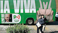 Turisti passano davanti al pullman del Partito Democratico che accompagnera' il leader e candidato premier Walter Veltroni nel suo tour elettorale in giro per l'Italia, davanti alla sede del partito a Roma, 15 febbraio 2008..Tourists walk past the Democratic Party's electoral campaign bus, in front of the party's headquarters in Rome, 15 february 2008. Candidate premier Walter Veltroni, seen in the picture at left on the bus, will cover by the bus the Italian territory for his electoral tour. Political elections are scheduled on next 13 and 14 april..UPDATE IMAGES PRESS/Riccardo De Luca