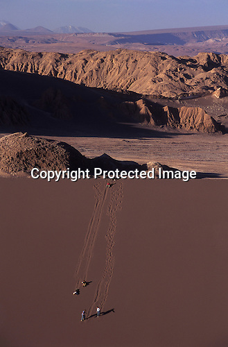 Tourist playing on huge sand dunes Atacama Desert Chile