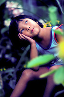 A young girl sits in the midst of green foliage looking up at the sky with her head resting on her hand.