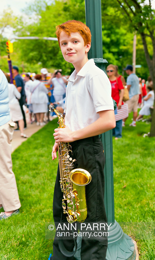 Red-haired boy with alto saxophone, after marching with his school band  the Merrick Memorial Day Parade on Monday, May 28, 2012, on Long Island, New York, USA. America's war heroes are honored on this National Holiday.