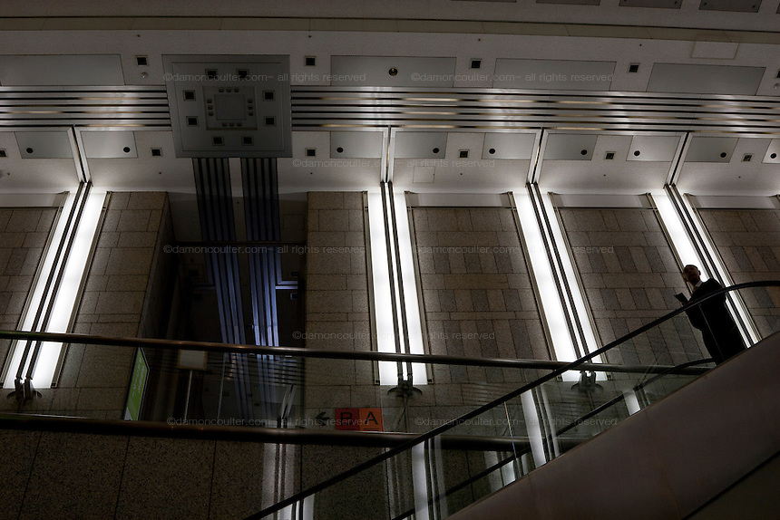 A man descends an escalator inside the Tokyo Metropolitan Government building. Shinjuku, Tokyo, Japan Wednesday, January 7th 2009