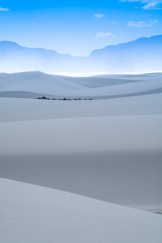Layers of dunes, a sandstorm, mountains and clouds in White Sands National Monument in New Mexico.