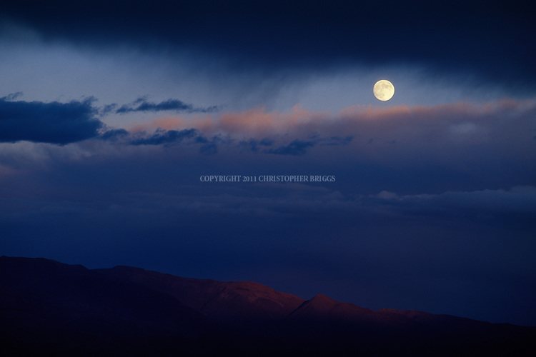 A clearing storm and moonrise at sunset over the Black Mountains in the Amargosa Range. Death Valley National Monument Est. February 11, 1933; Death Valley National Park in 1994. 5,270 square miles (13,649 km2). Inyo County, CA.