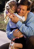 A smiling father hugs his young daughter.