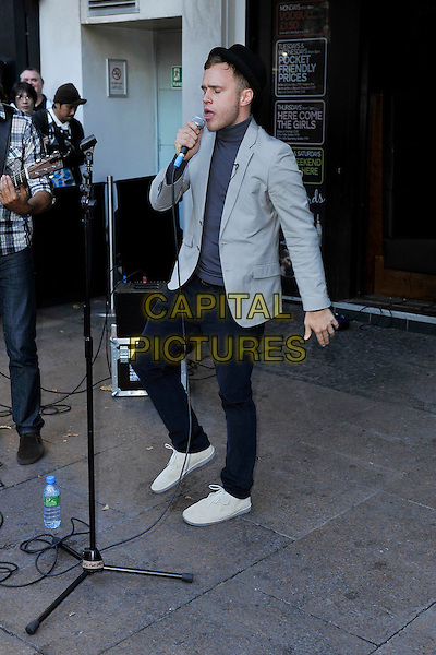OLLY MURS.Seen busking in Leicester Square, London, England, UK, .October 11th 2010..full length music concert gig performing performance microphone singing black pork pie hat grey gray blazer jacket blue polo neck trousers white shoes .CAP/MAR.© Martin Harris/Capital Pictures.