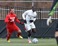 University of Connecticut forward Stephane Diop (5) looks to pass as University of New Mexico midfielder Levi Rossi (16) defends..NCAA Tournament. With a goal in the second overtime, University of Connecticut (white) defeated University of New Mexico (red), 2-1, at Morrone Stadium at University of Connecticut on November 25, 2012.