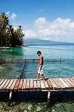 FRENCH POLYNESIA. Tevaiti, walking along a dock on Atger Island. A small private island owend by his family.